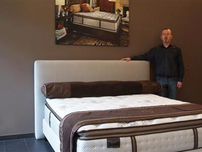 Nico Dhur, owner of House of Comfort, next to a luxurious bed